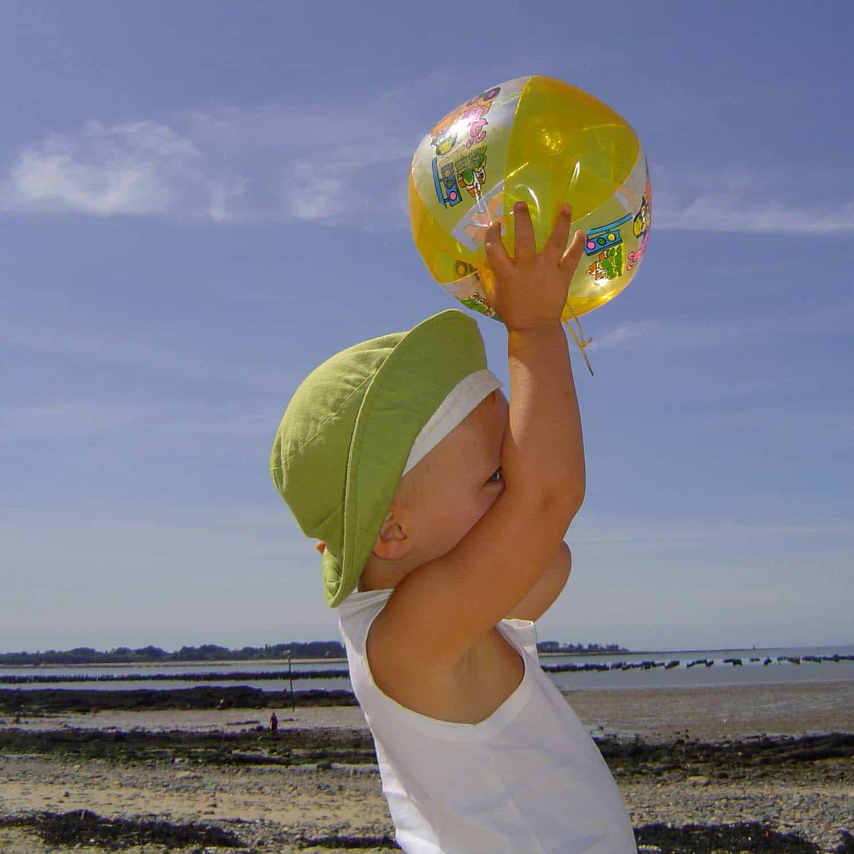 Enfant au ballon sur la plage, portrait